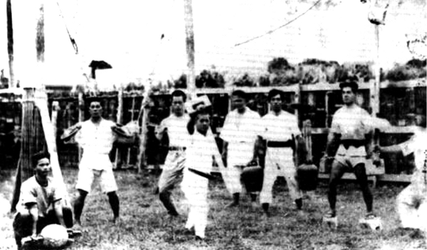 Using auxiliary exercise (hojo undō) equipment of Karate-jutsu in the rear of Mabuni Kenwa's house:  Madanbashi Keiyō (2nd from left), Shinzato Jin'an (4th from left), Chōjun Miyagi (5th from left)