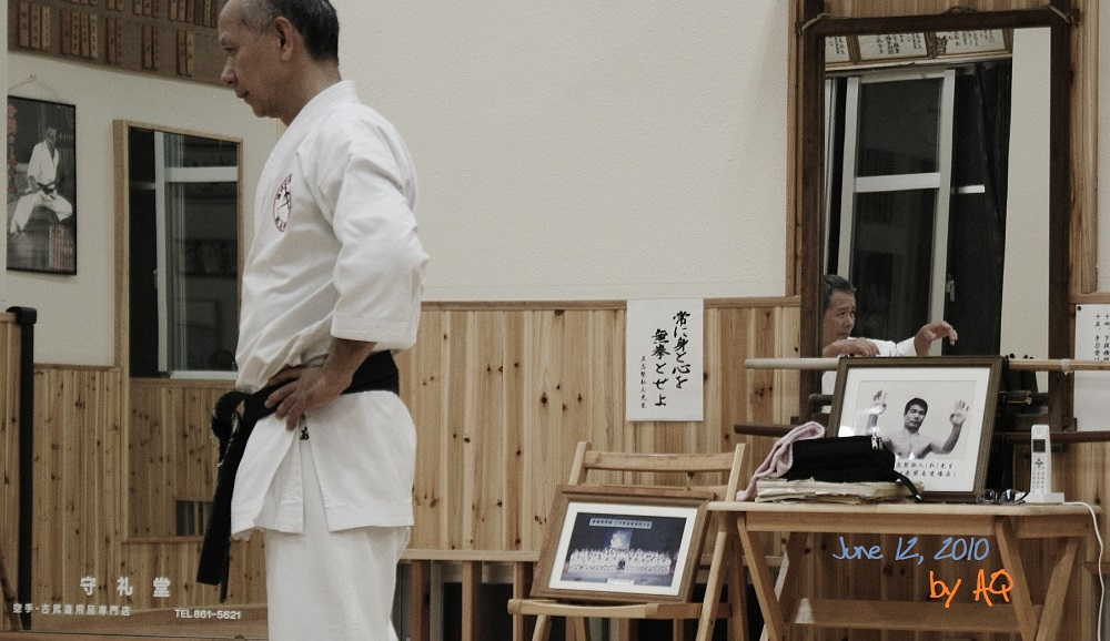 June 12, 2010, Akamine Sensei at Mukenkan / Shinbukan Dojo, Okinawa. I like the multiple levels of this photo, generated by mirrors, lights, decor, and persons. Photo. A. Quast