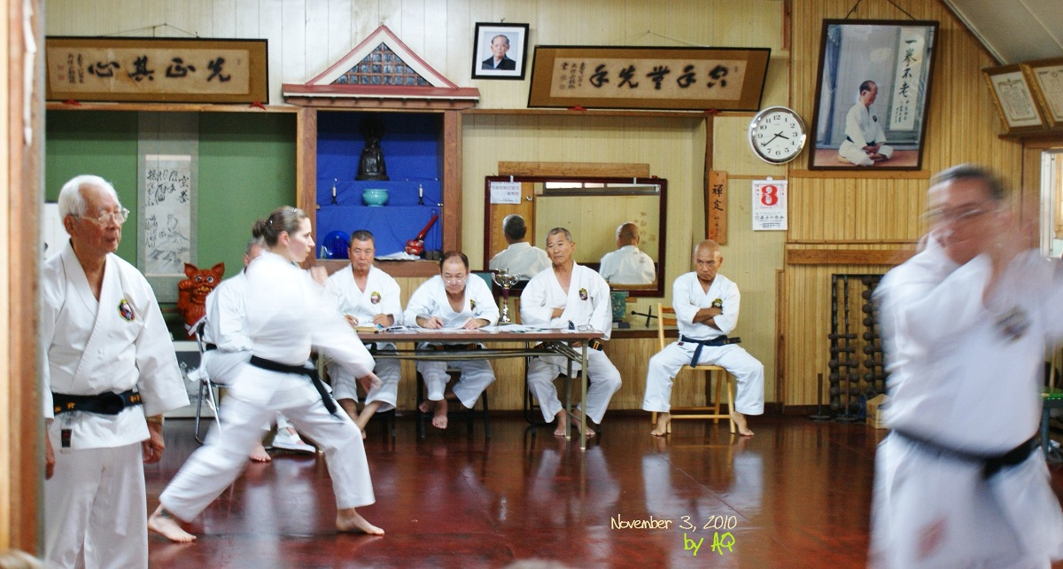November 3, 2010, during the gradings at Nagamine Kodokan Honbu in Naha Kumoji, Okinawa. From l. to r.: Kuniyoshi Sensei (a most respectable gentleman and performer), Australia's Bec Sheather grading, Taira Yoshitaka Hanshi 10th Dan, Nagamine Takayoshi Hanshi 10th Dan, Higa Nobuhide Hanshi 10th Dan, Shinjo Kiyoshi Hanshi 9th Dan.