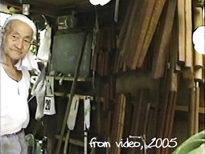 Okinawa master weapons craftsman Kami Unten in his workshop with Bo, Nunchaku, Tonfa etc. on the wall. In the back of his workshop he grew orchids in dozens. Photo taken from a video courtesy of Katherine Loukopolo.