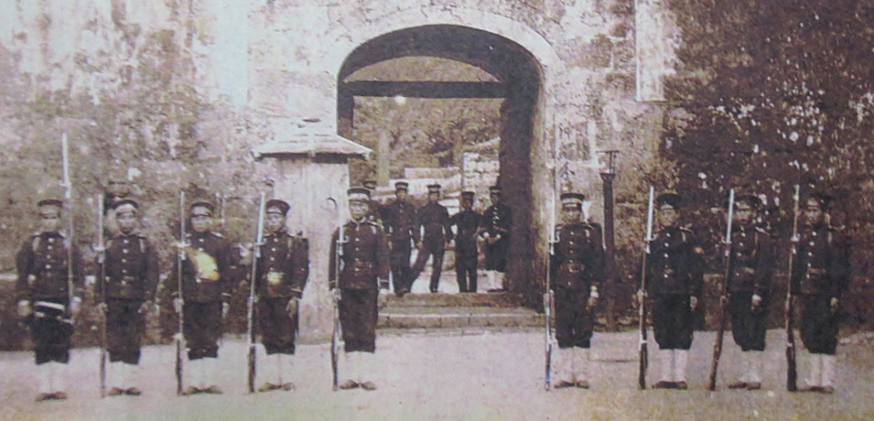 Soldiers of the Kumamoto Garrison with bayonet rifles (jūken) in front of the Kankaimon front gate of Shuri Castle. Following the Ryūkyū Shobun, the Kumamoto Garrison had been sent by the Meiji government and was lodged inside Shuri Castle.